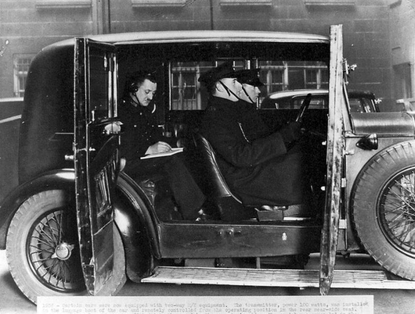 Officers in an early wireless car primed for response receiveing a morse code message from Information Room